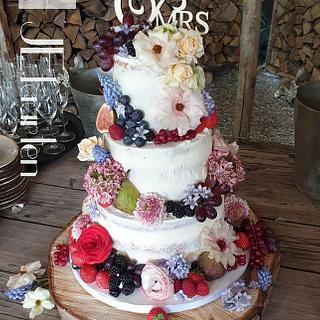 Semi naked weddingcake, with fresh flowers and fruits