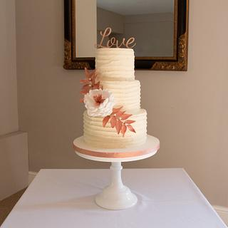 Buttercream wedding cake with open peony and rose gold foliage