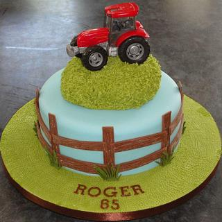 Red tractor birthday cake with wooden fence and grass hill