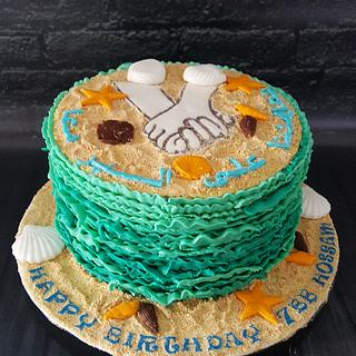 Sea waves cake with hands holding each other in the sand