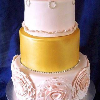 pink and gold wedding cake with large frill flower