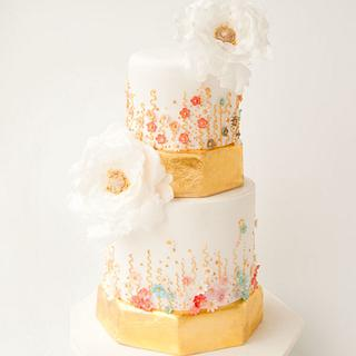 a gold wedding cake with pastel blossoms and white peonies