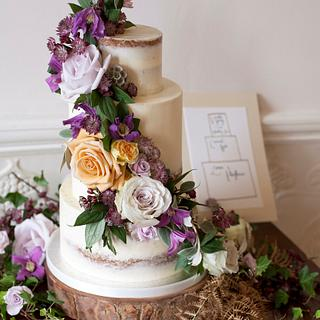Semi-naked wedding cake with purple and amber fresh flowers
