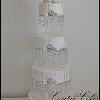Tall wedding cake on crystal stand.