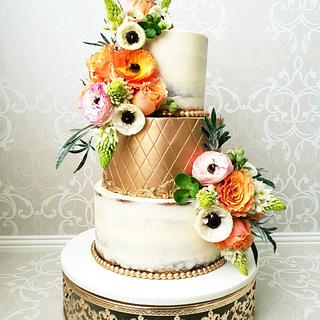 Semi naked,solid gold wedding cake dressed with fresh flowers