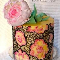 Royal icing design on the cake with a peony flower on top