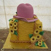 Hay bale, cowgirl hat and sunflowers