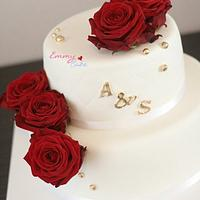 White wedding cake with red roses and a touch of gold