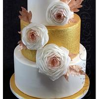 golden wedding display cake with ranunculuses