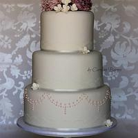 Wedding cake with purple ruffle flowers and beaded swags