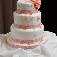 Coral blossom and pearl cascade wedding cake with coral ribbon and lace overlay by Kathryn