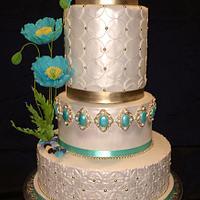 Teal poppy flowers on a wedding cake