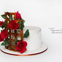 Cake with a rose at a wattle fence