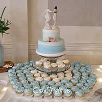 A cutting cake and cupcakes for a beach Wedding