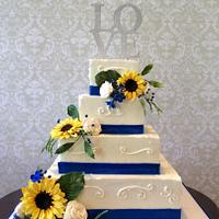Wedding Cake with sunflowers, white roses and blue accents.
