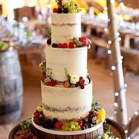 Semi naked wedding cake with fresh fruit and flowers