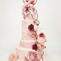 Pink and peach wedding cake with roses and orchids