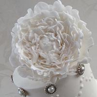 White peony cake on raindrop crystal stand