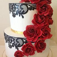 black and white wedding cake with red sugar roses