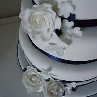 Navy & white wedding cake with roses, blossom & butterfly details