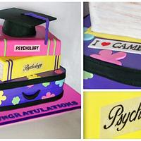 stacked books and a suitcase graduation cake