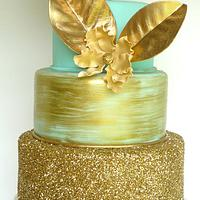 Gold and seafoam green wedding cake and dessert table