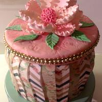Pleaded prints wafer paper cake with a gumpaste peony.
