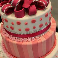A pink birthday cake with big bow on top