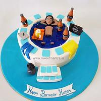 Guy relaxing in Jacuzzi/Pool shaped fondant cake with Bira beer bottles for husband's birthday