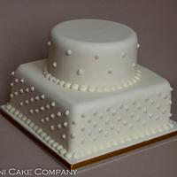 Two tiered ivory wedding cake with pearls