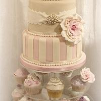 Whimsical striped cake with bow and cupcakes
