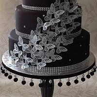 black and silver butterfly cake on homemade cake stand