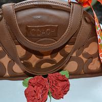 Brown coach bag and carnation.