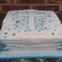 Christening cake with stencil cross and scattered heart confetti