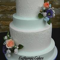 Pale blue and white wedding cake with sugar flowers