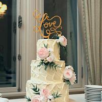 Cream wedding cake with pink and white ranunculuses and wooden topper