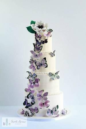 White wedding cake with purple butterflies cascade - Cake by Sweet Avenue Cakery